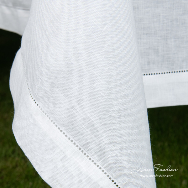 Border of white linen blend tablecloth with hemstitch