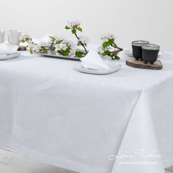 White linen tablecloth with flower ornaments, folded border