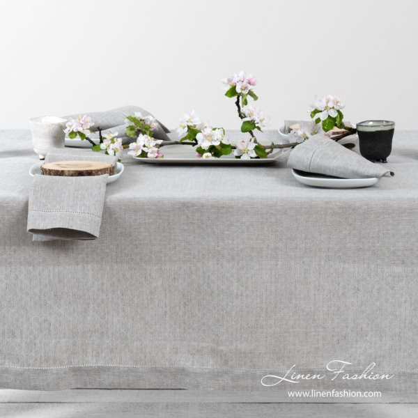 Light grey pure linen tablecloth in a small openwork pattern, and decorated with a row of hemstitch along its edges