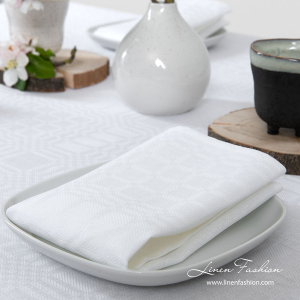 Playfully patterned optical white napkin made from medium weight linen / cotton fabric
