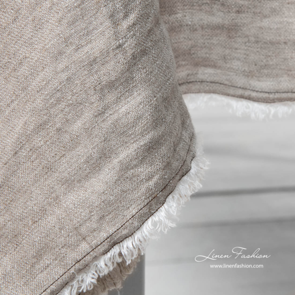 Light grey tablecloth's edge with brown stitches and fringe