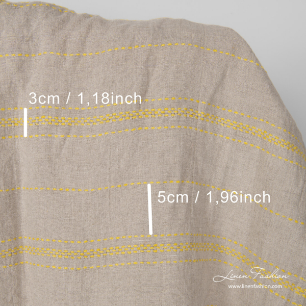 Yellow running stitch spacing measures on washed linen fabric