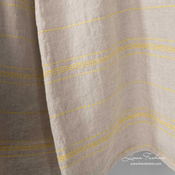 Natural linen fabric decorated with yellow stitches