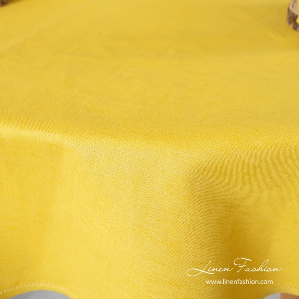 Yellow colored tablecloth, round.
